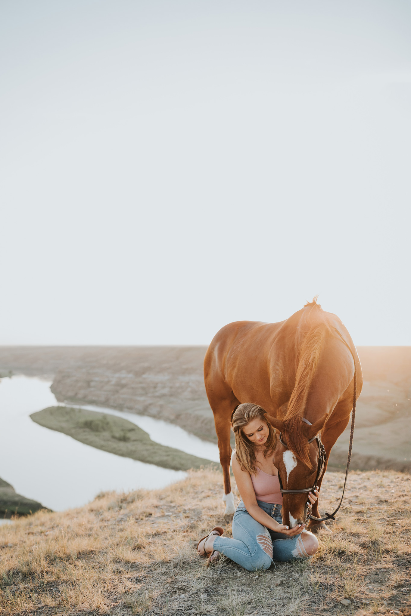 girl sits beside horse at sunset view of coulee river