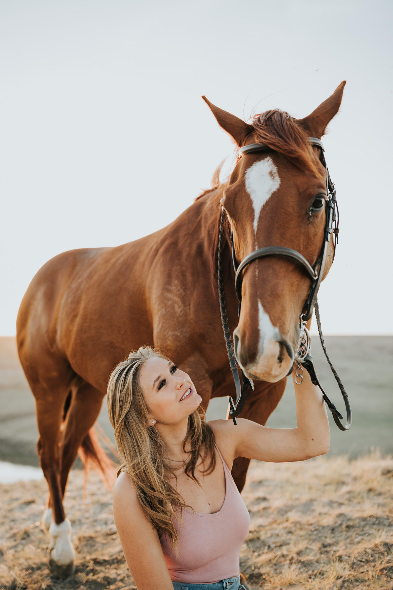 equine photo girl sitting beside horse smiling
