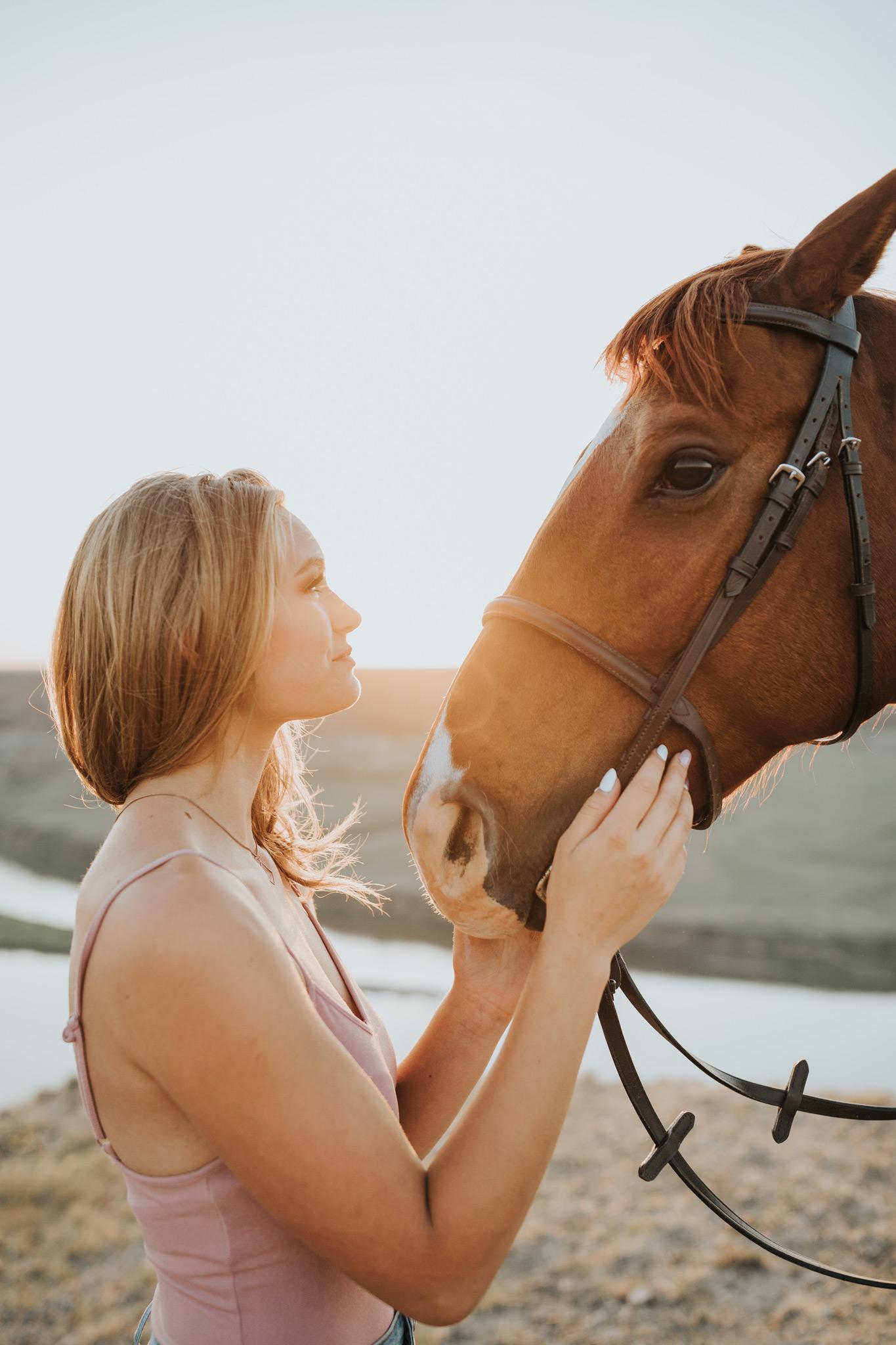 girl looking into horses eyes alberta sunset