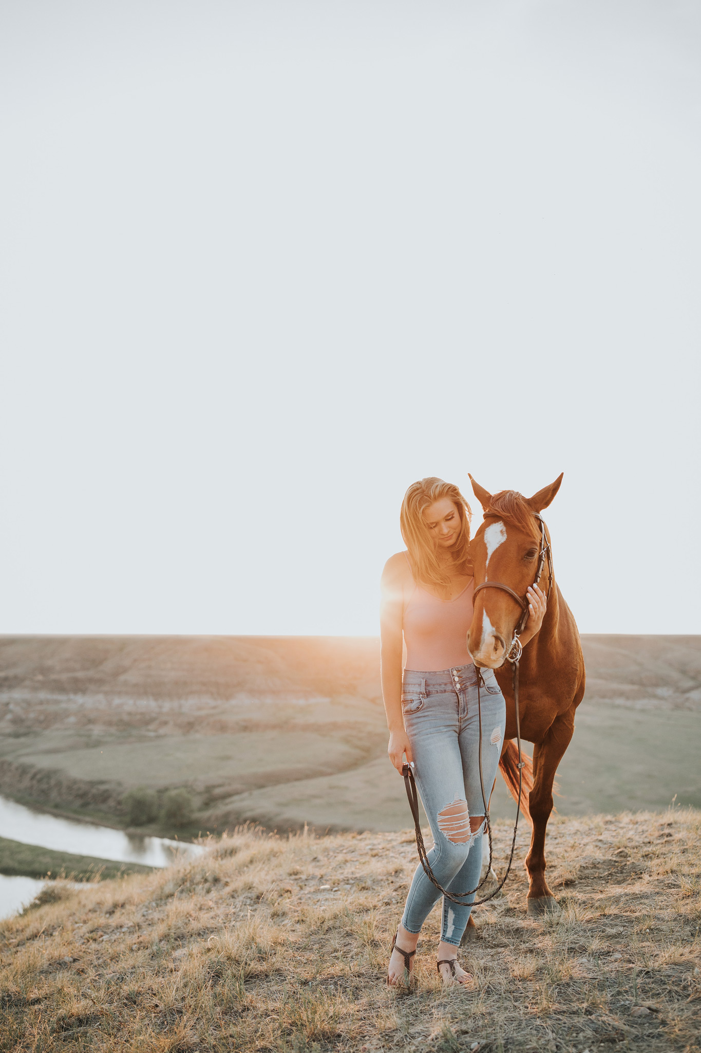 girl standing beside horse at sunset