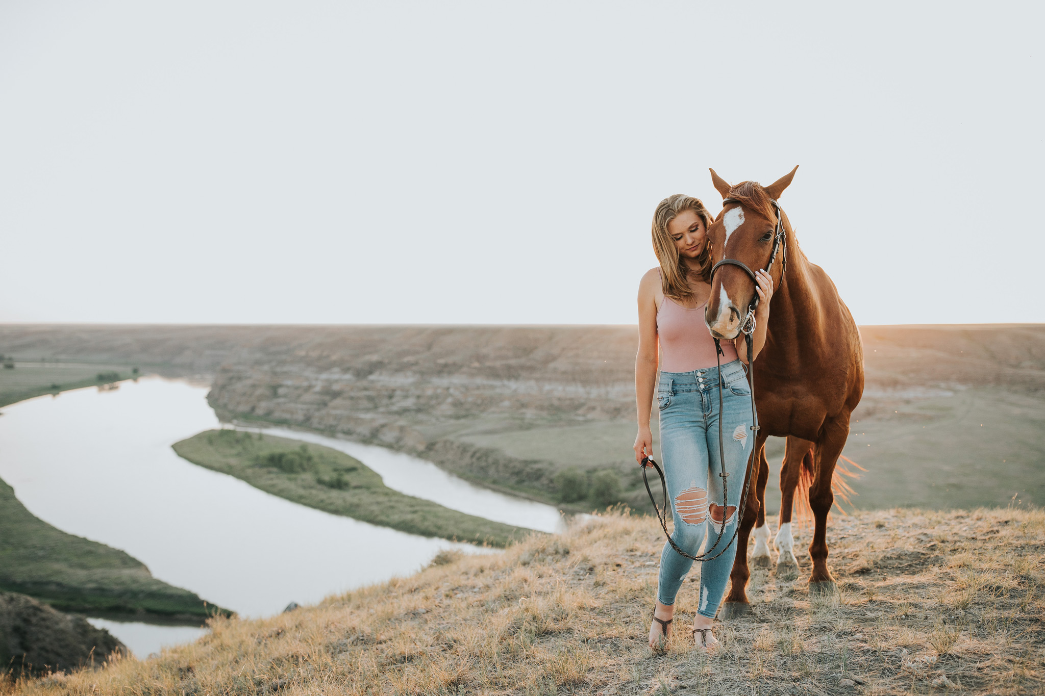 girl standing beside horse view of coulee and river