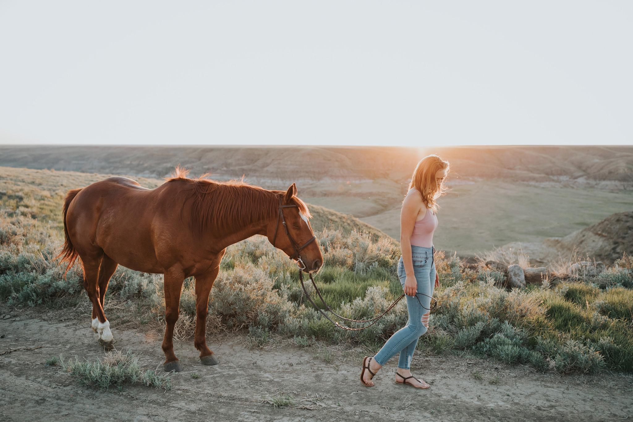 girl walking horse at sunset