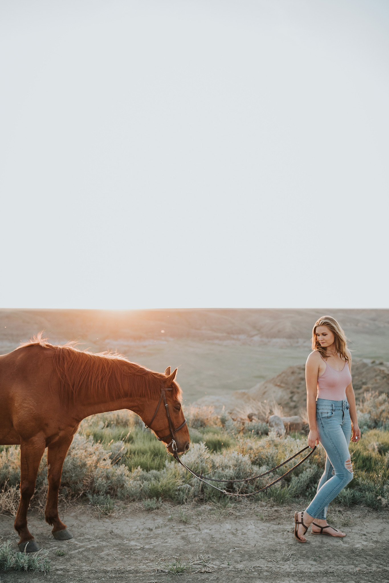 girl walking horse at sunset looking back