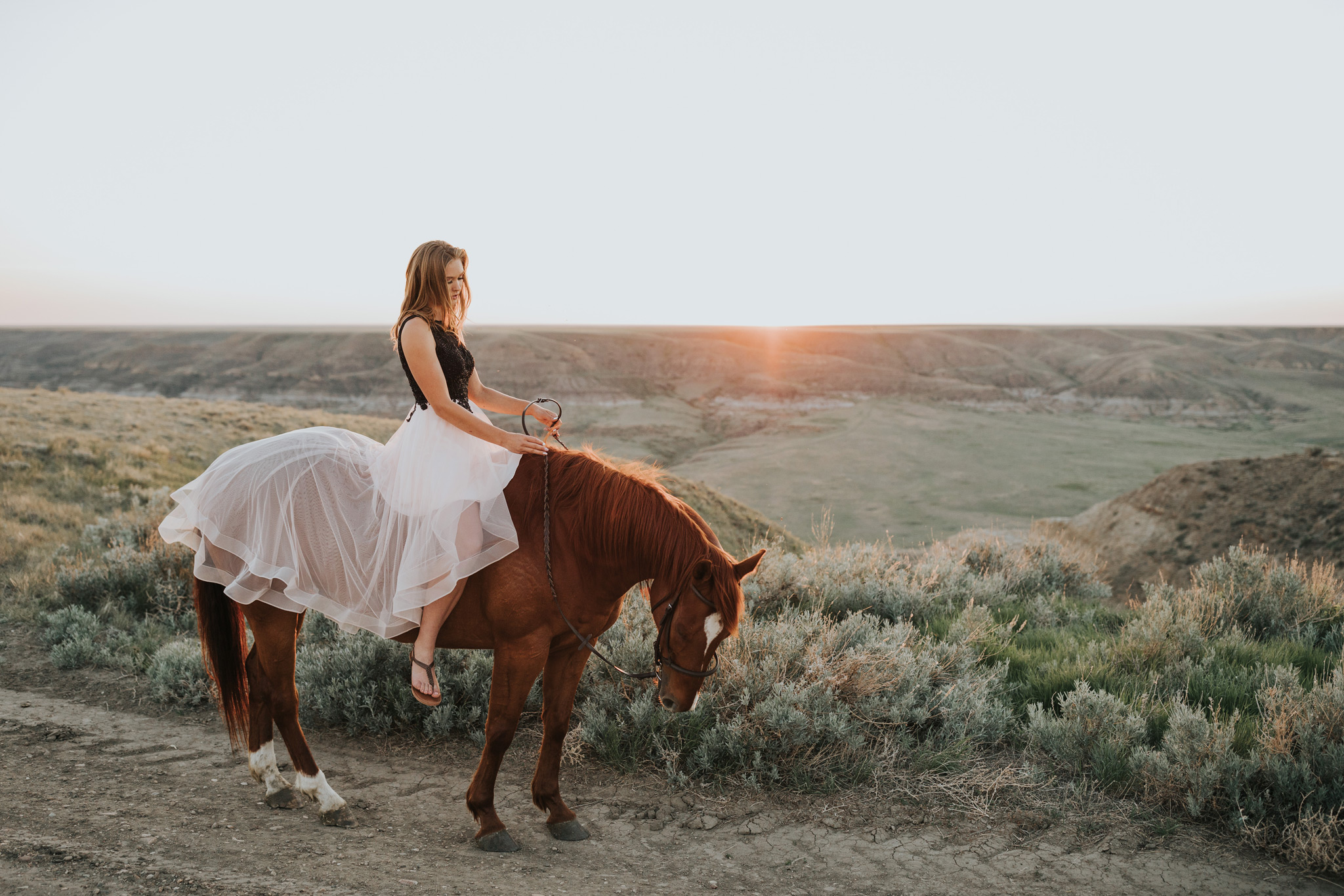 girl in grad dress on horse at sunset