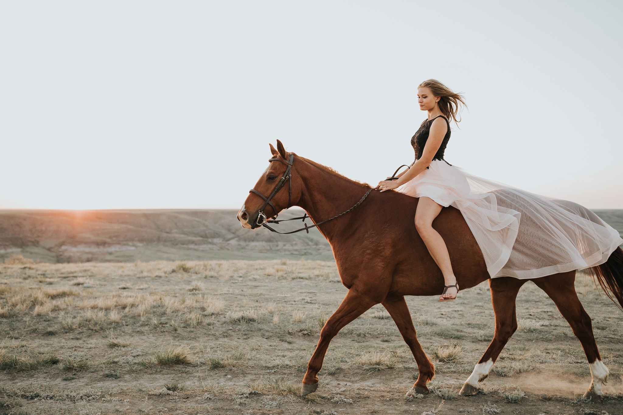 girl wearing prom dress riding horse