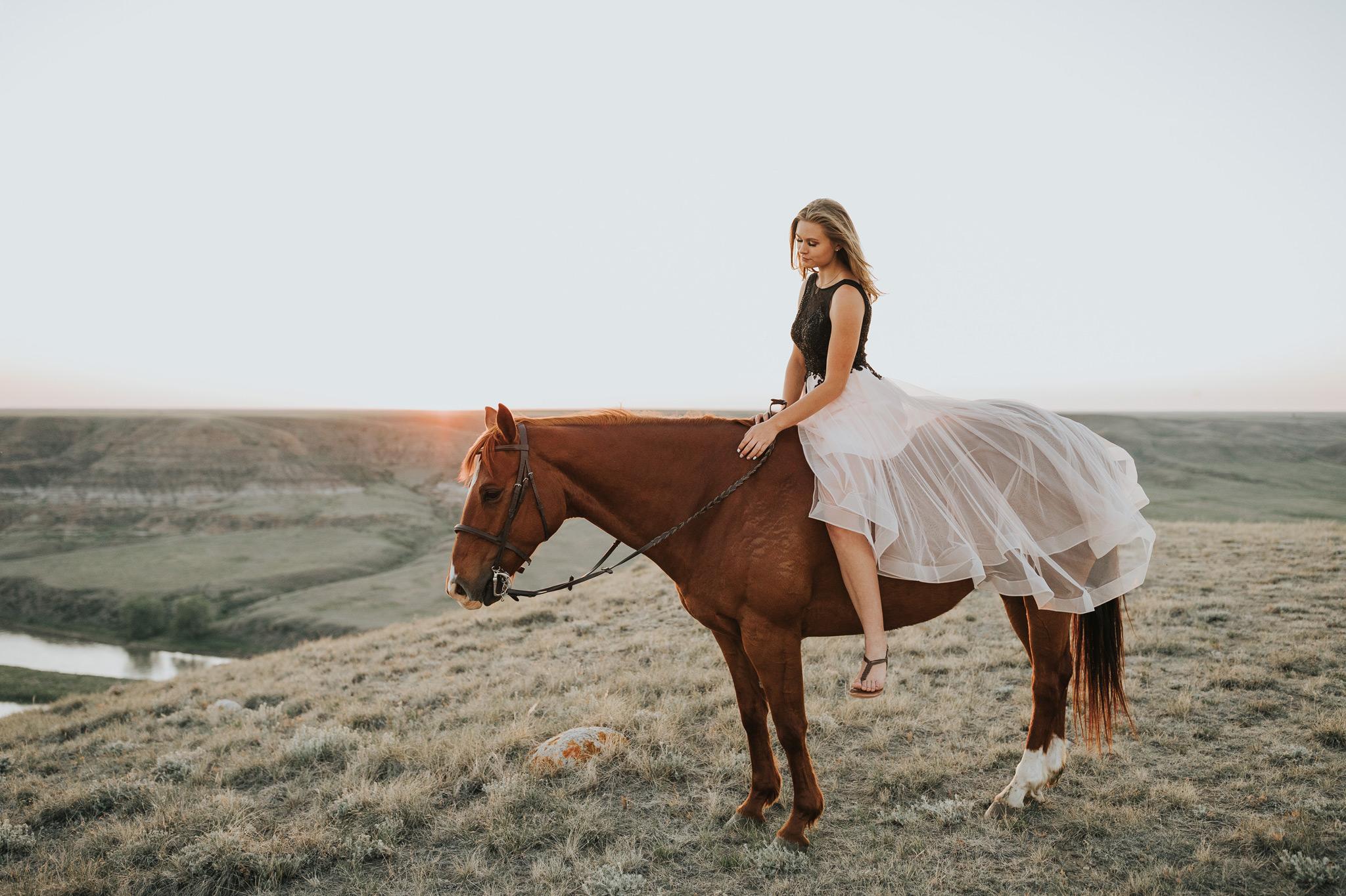 girl in flowy grad dress sitting on horse skirt draped over