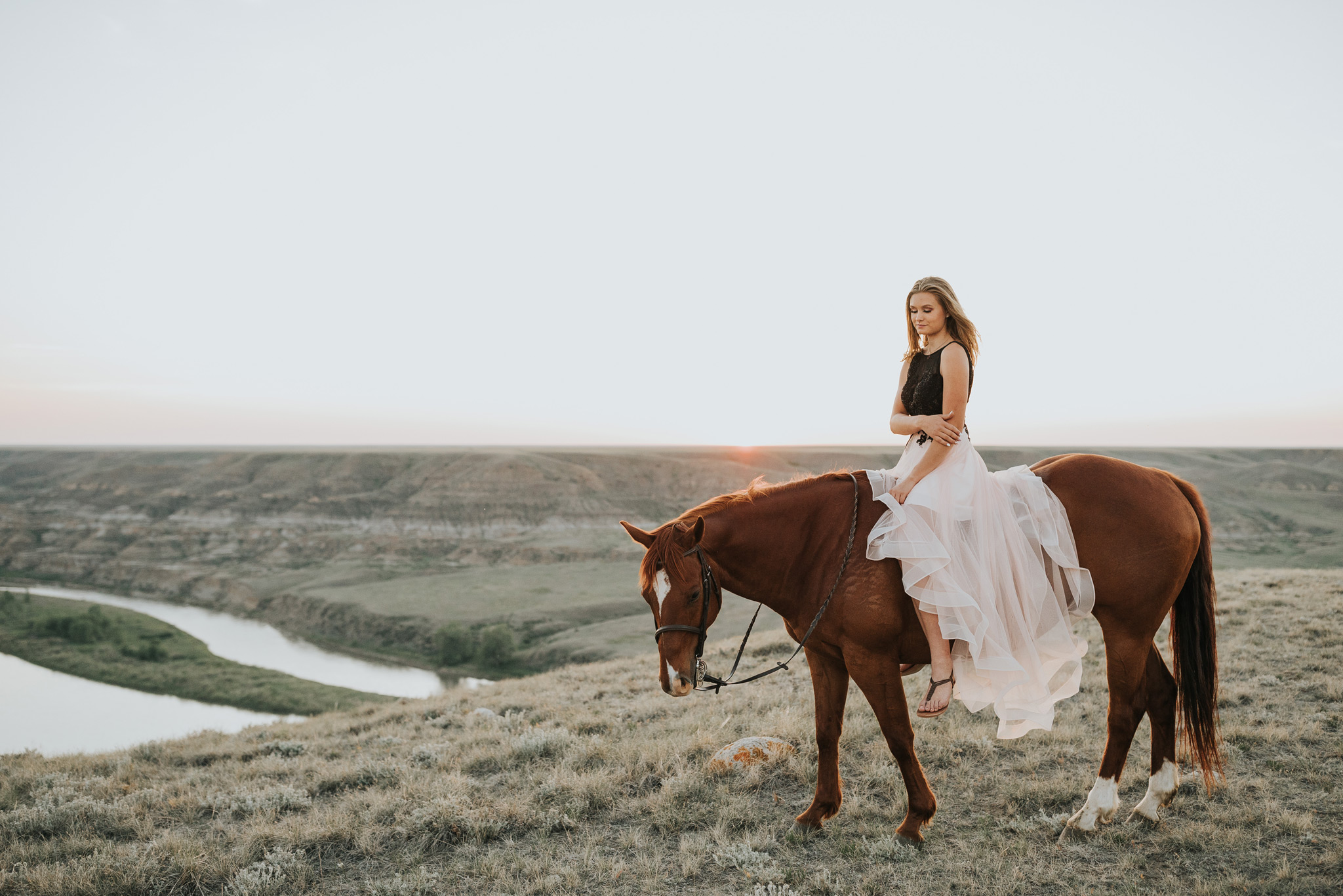 girl in prom dress sitting on horse