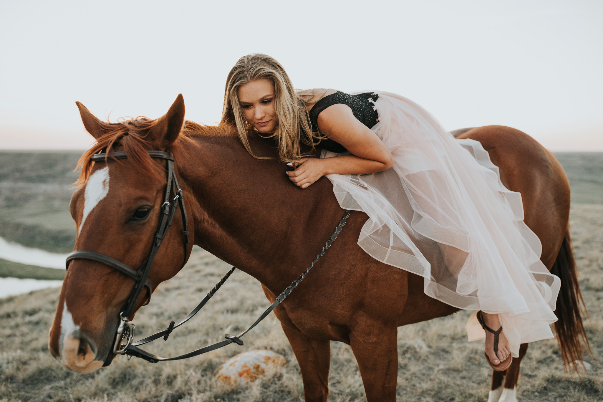 girl in prom dress laying on horse