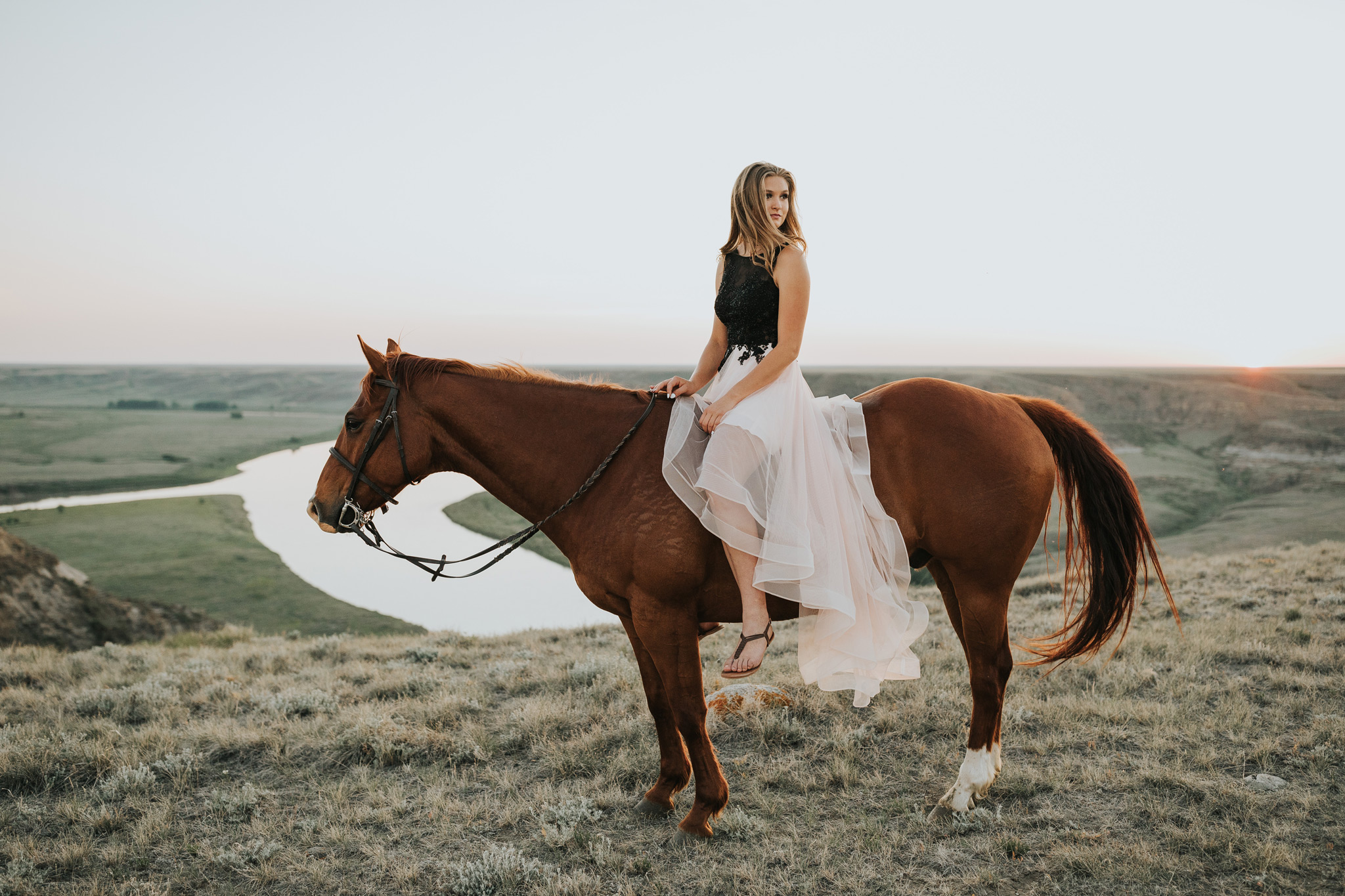 girl in prom dress sitting on horse looking back