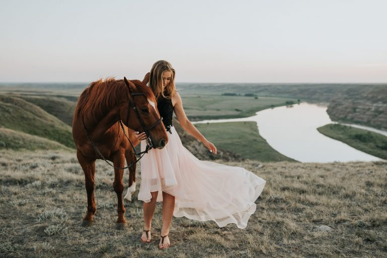 girls prom dress blows in wind standing beside horse