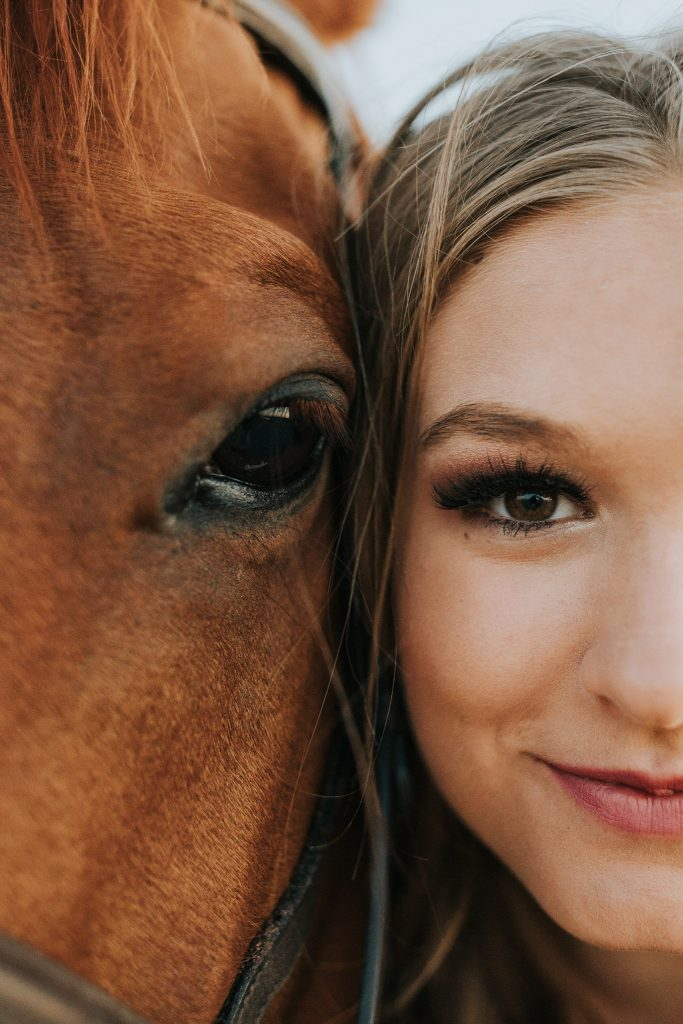 closeup of girl and horse faces together