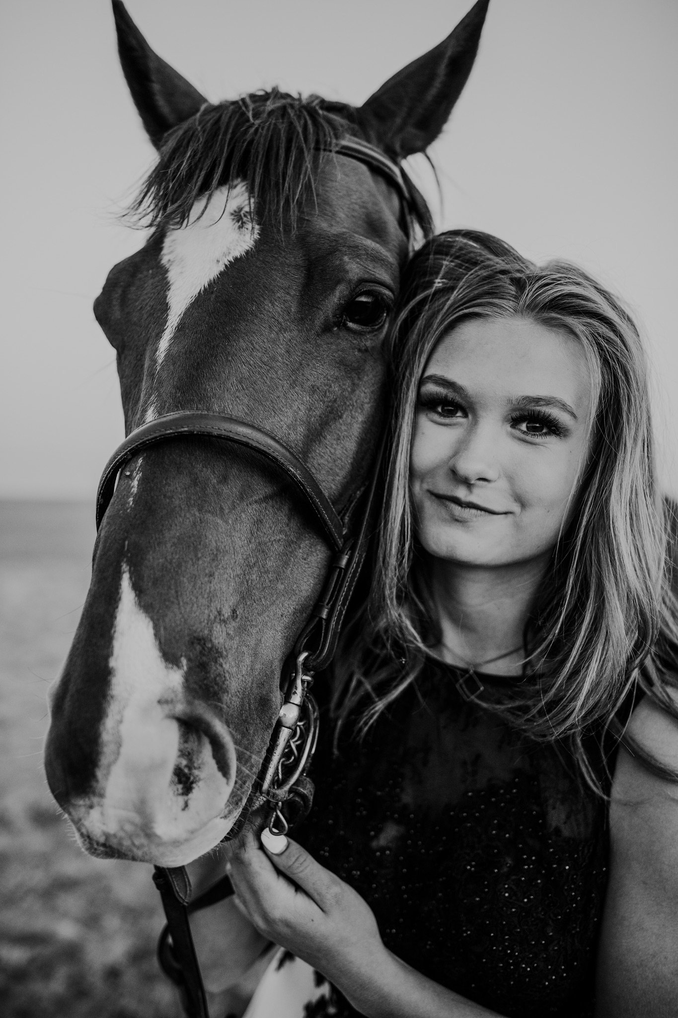 girl standing beside horse closeup black and white