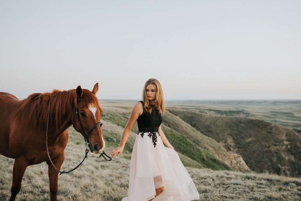 girl in prom dress walking her horse