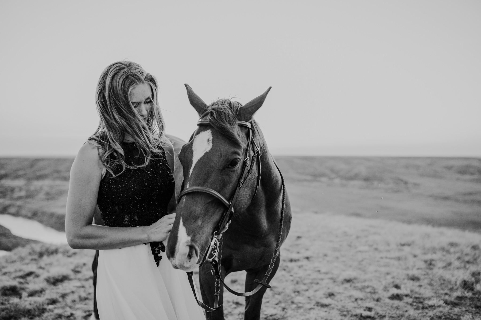 grad girl standing beside and petting horse