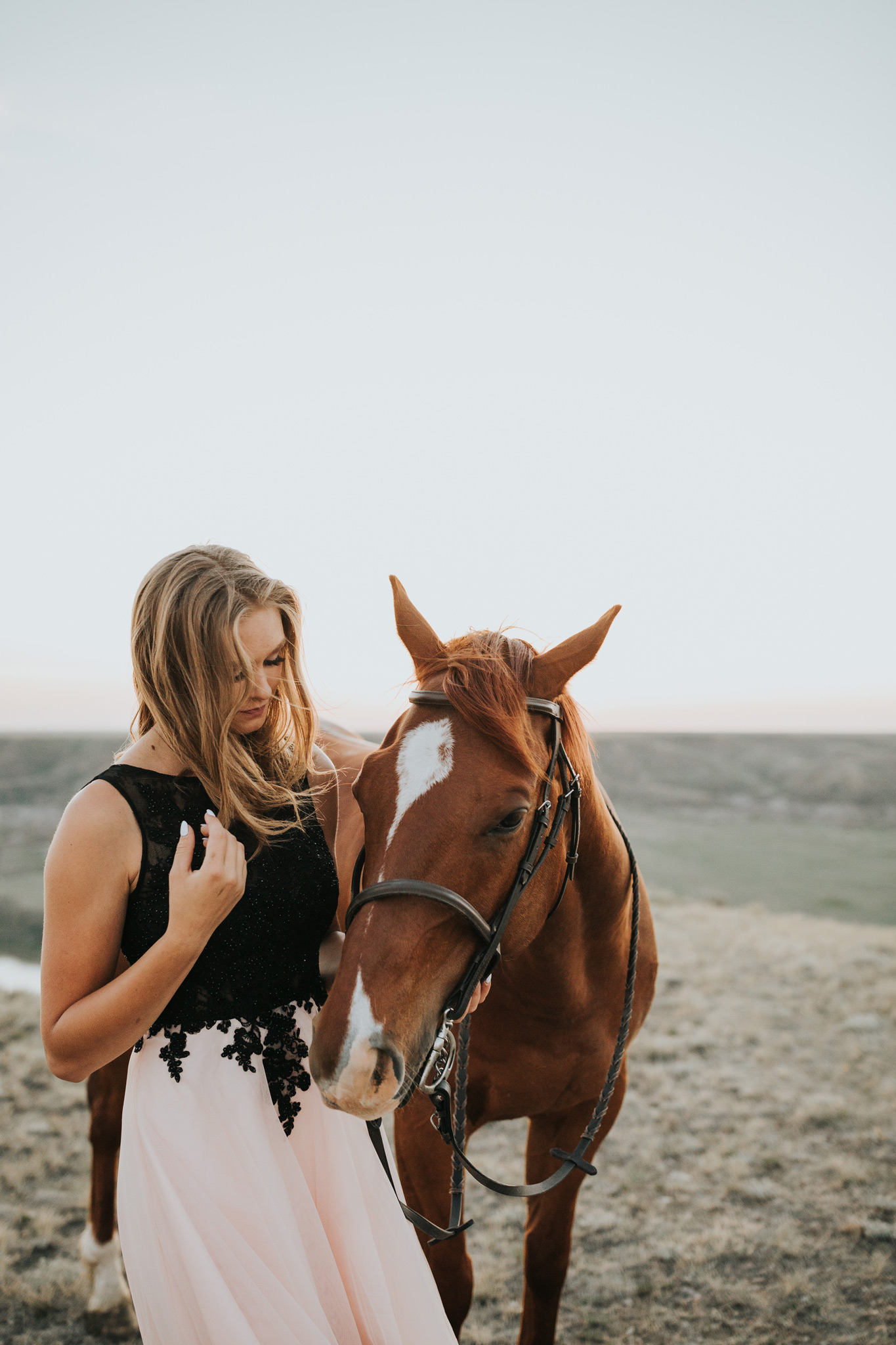 grad girl standing beside horse hair blowing in wind