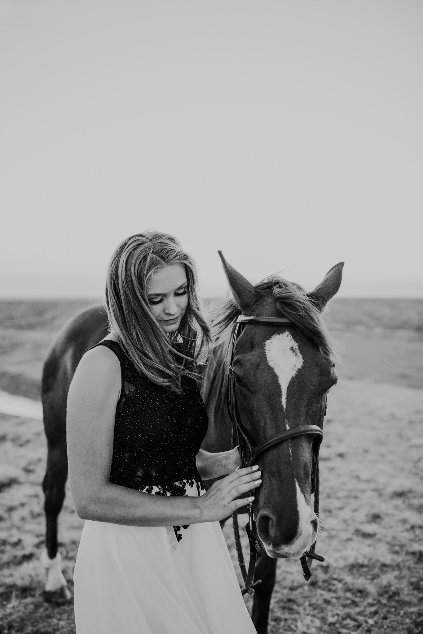 grad girl petting horse hair blowing in wind black and white
