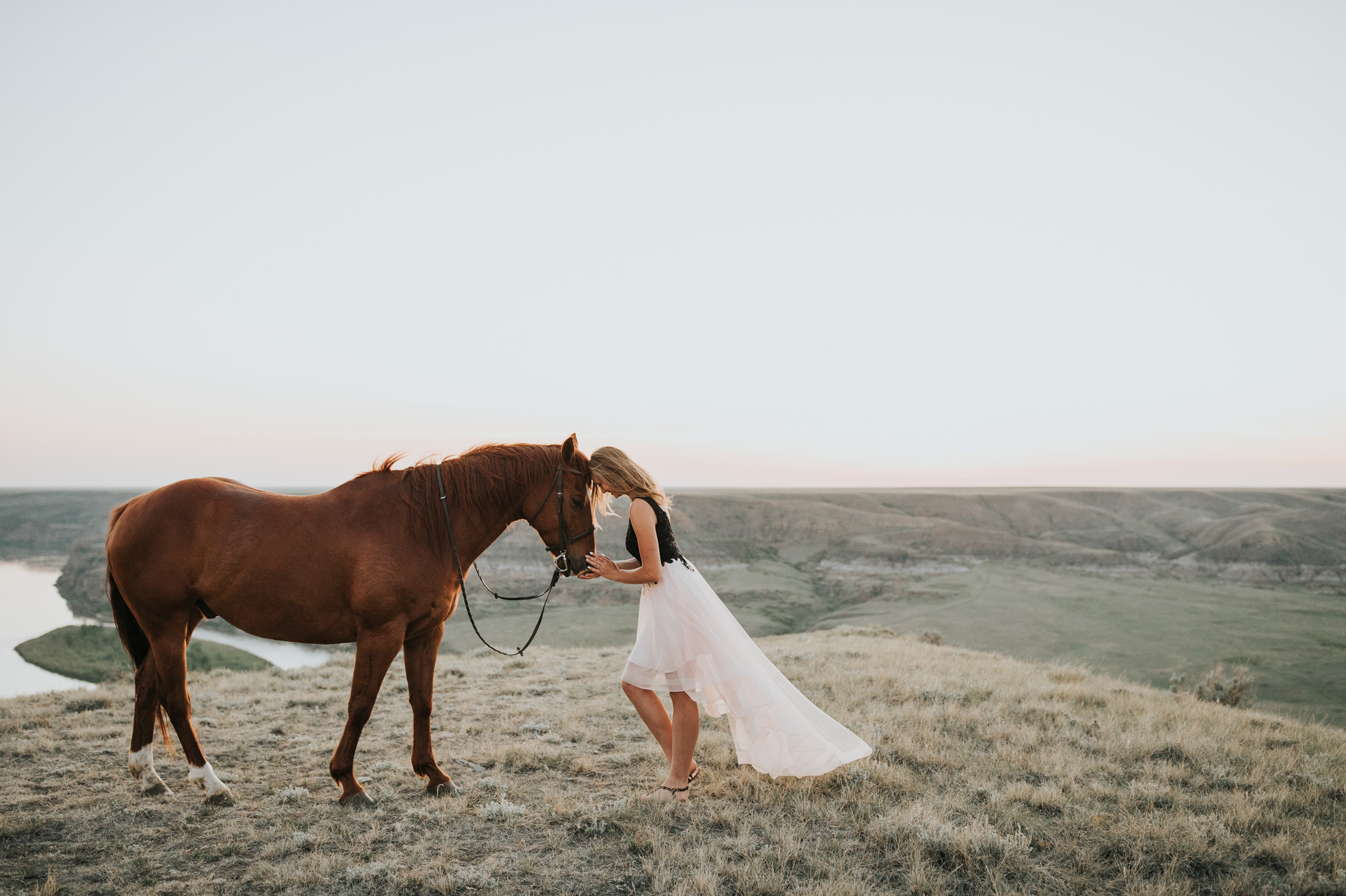 grad girl in flowy dress touching forehead to horse