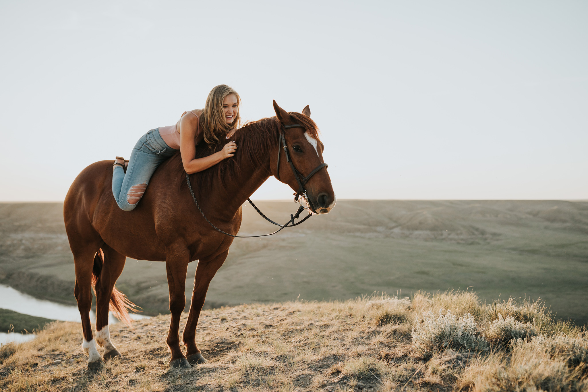 girl laying on horse laughing