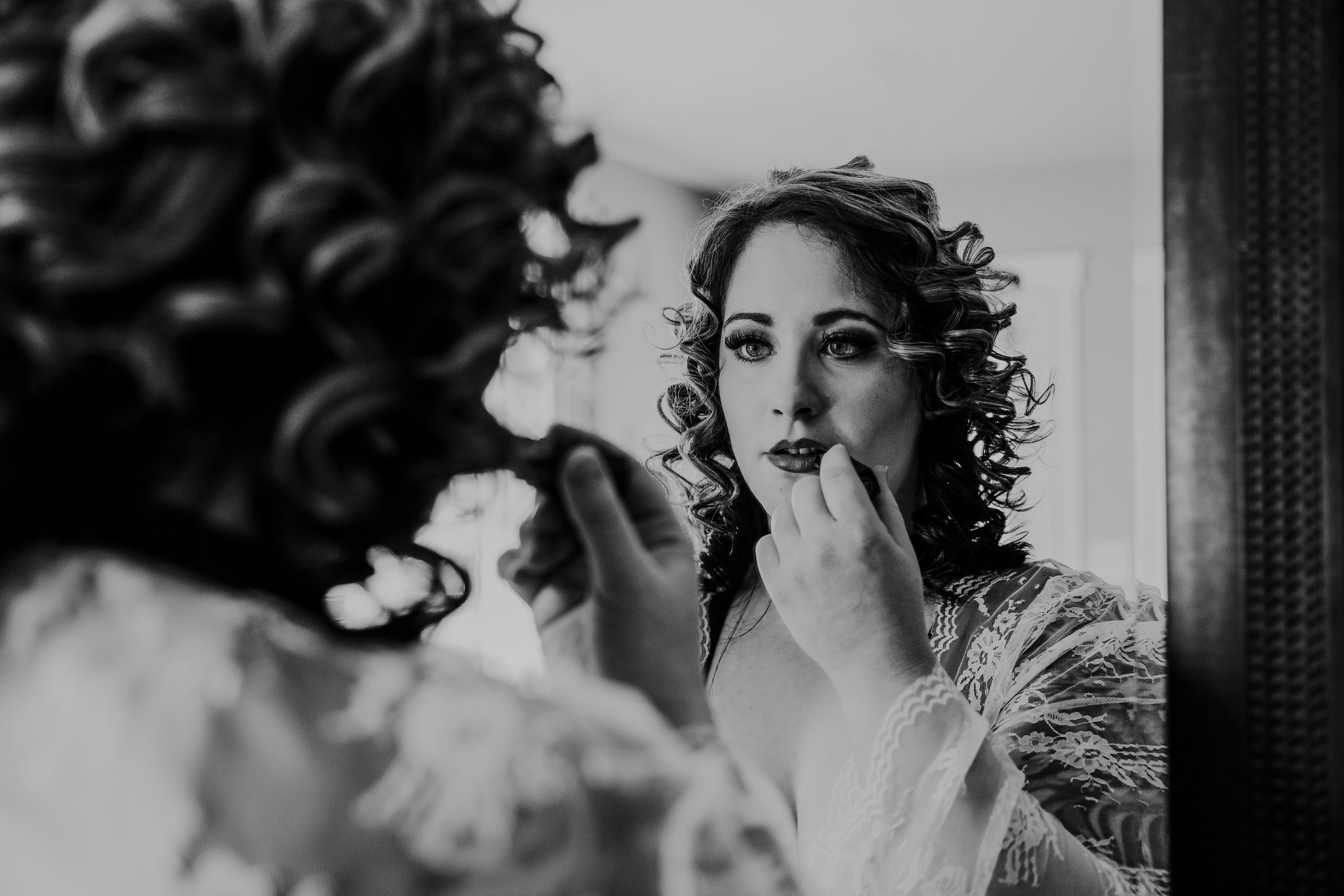 woman applying lipstick in mirror bridal boudoir medicine hat