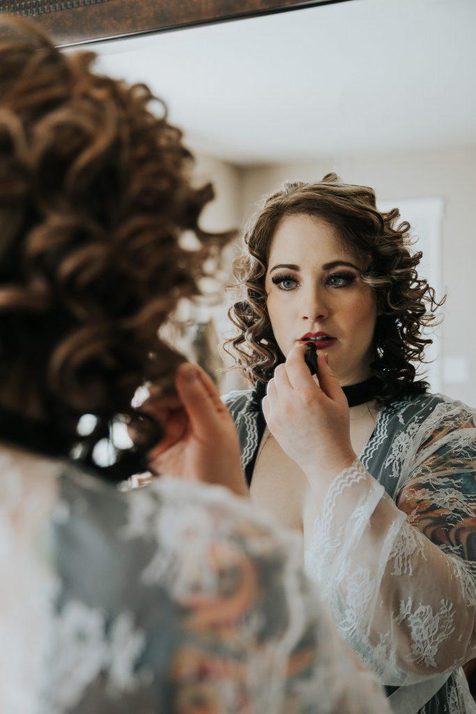woman applying lipstick in mirror bridal boudoir alberta