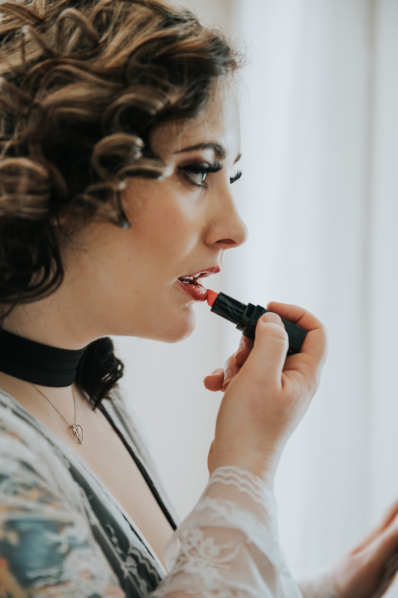 woman applying lipstick in mirror bridal boudoir photo