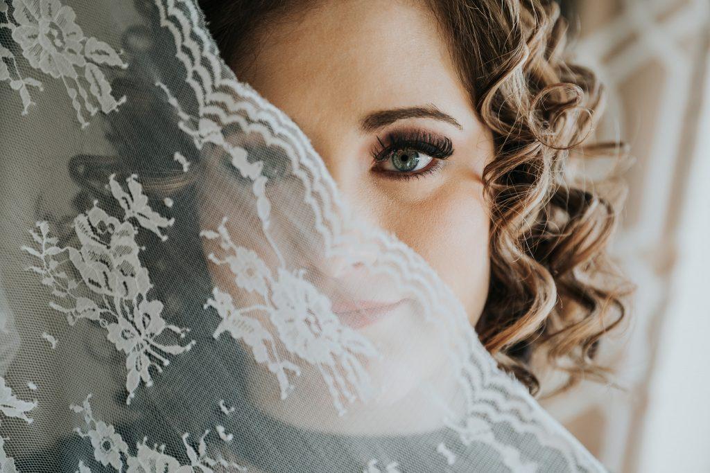 bride with lace veil half covering face boudoir photo