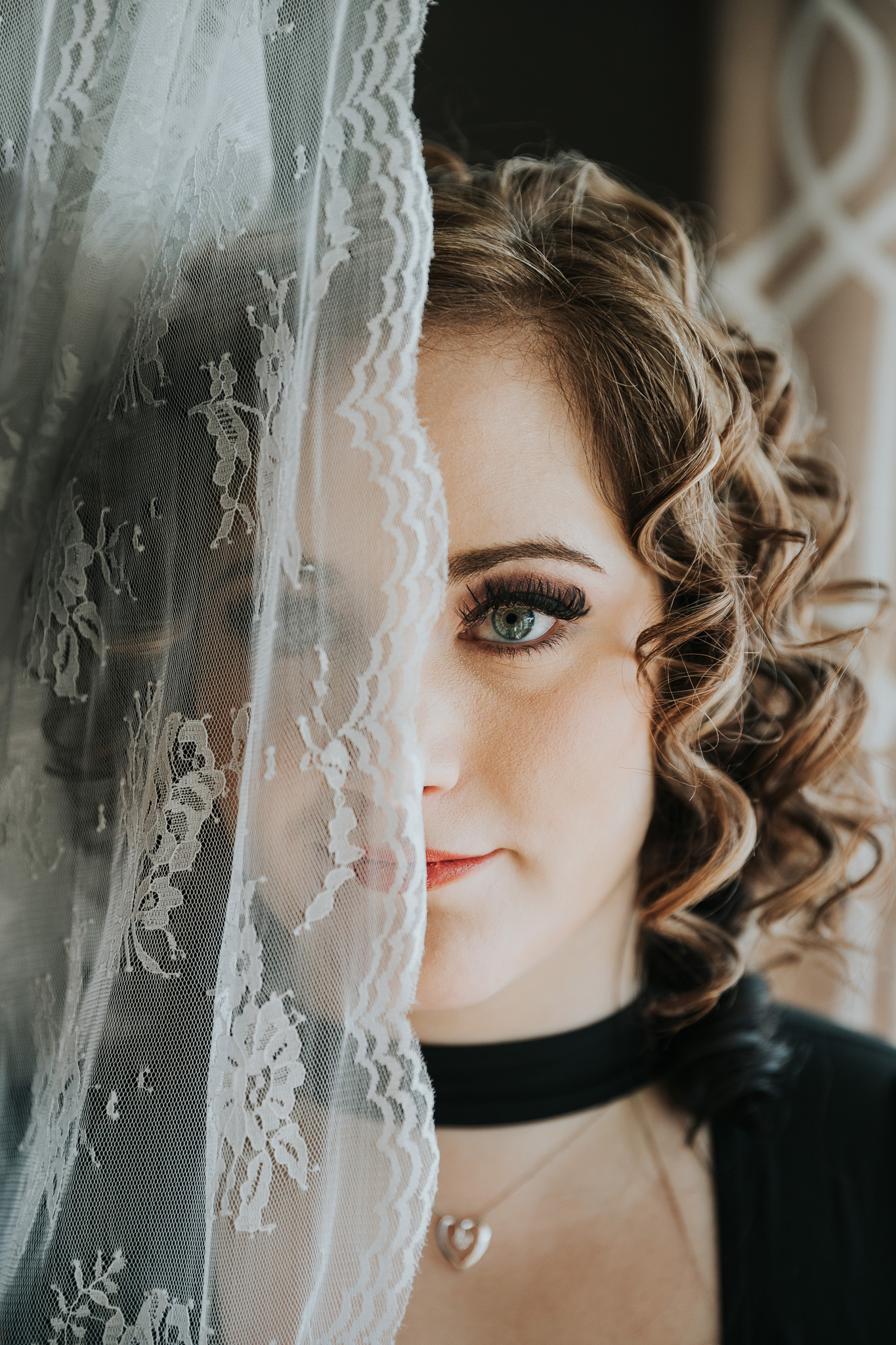 bride with lace veil half covering face boudoir photo