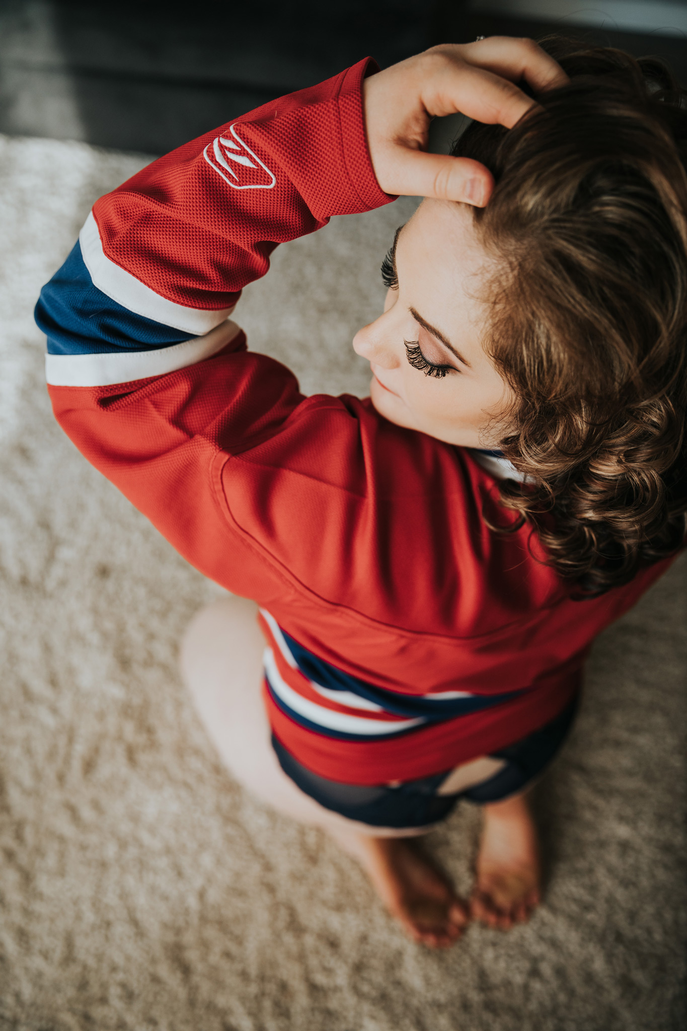 woman sitting on floor wearing hockey jersey bridal boudoir