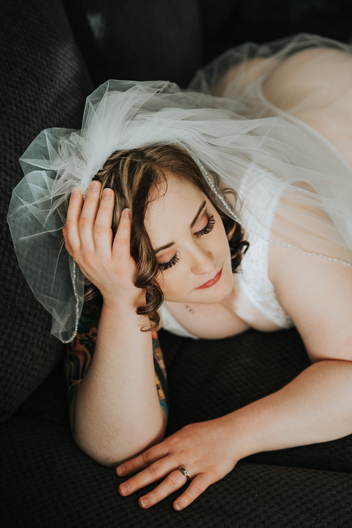 woman lying on couch wearing veil bridal boudoir
