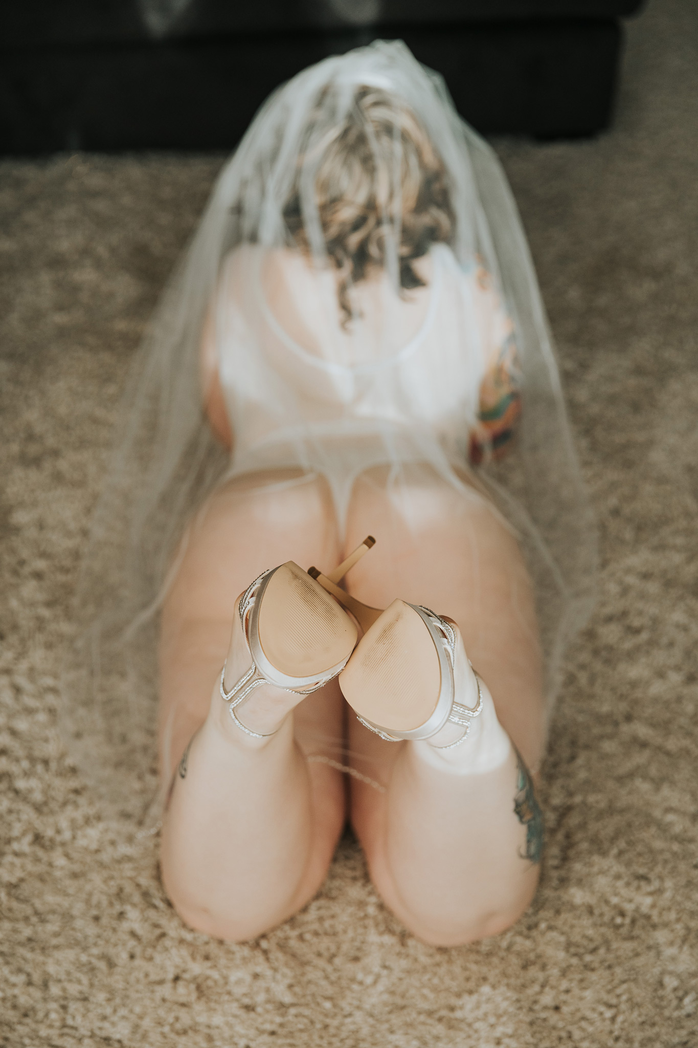 woman lying on floor in heels wearing veil bridal boudoir photo