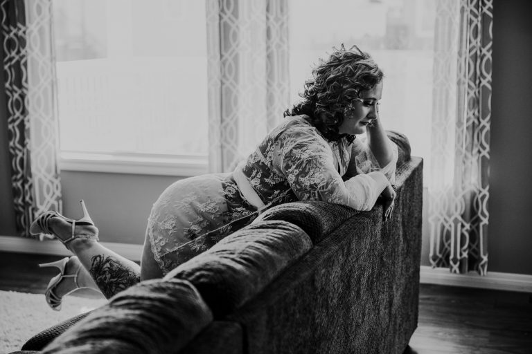 woman sitting forward on couch white lace robe bridal boudoir