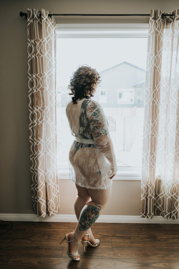woman in white robe and heels standing in front of window bridal boudoir