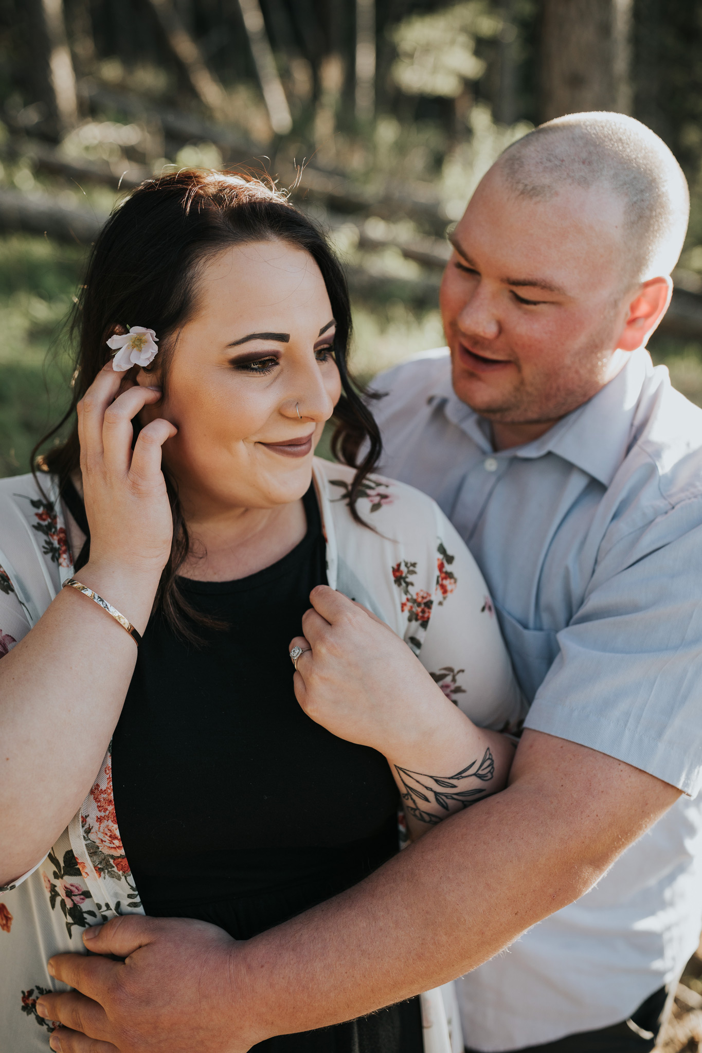 man embraces fiancé as she brushes hair behind ear