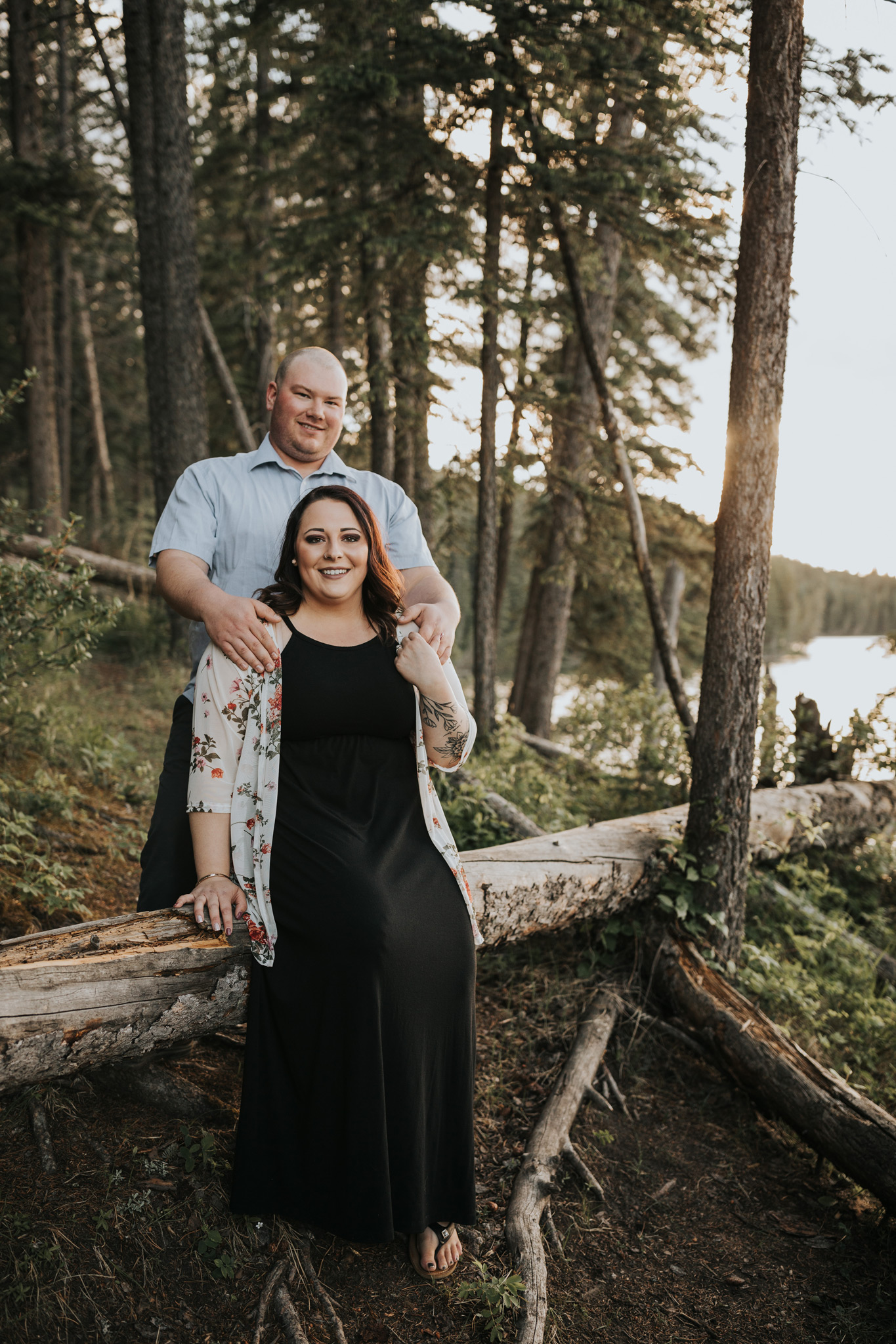engaged couple smiling sitting on fallen tree reesor lake