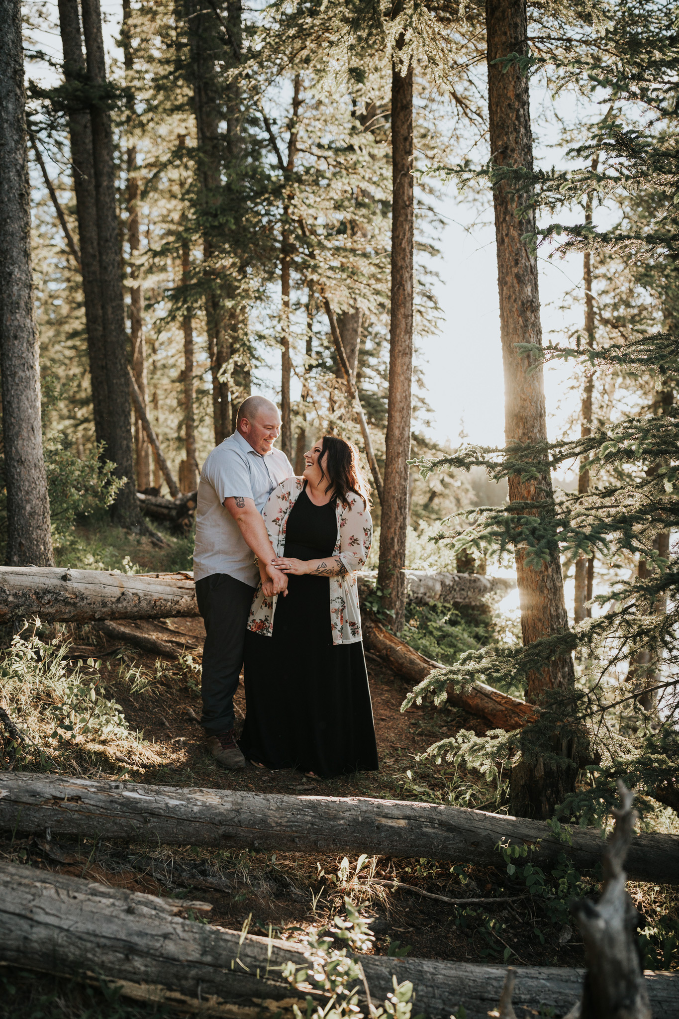 couple standing together laughing in forest cypress hills alberta engagement