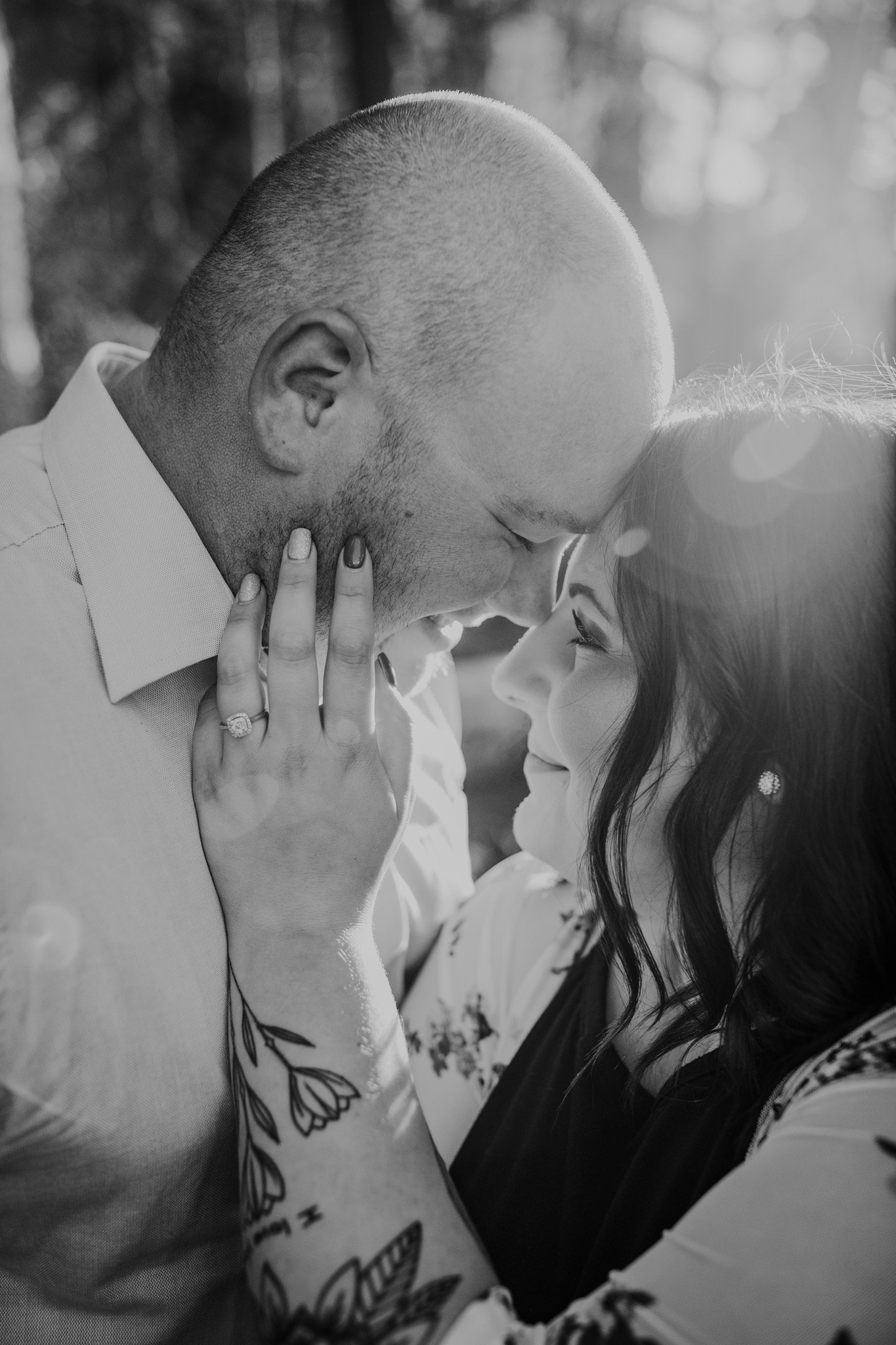 woman touches fiancé's face with ring hand romantic photo