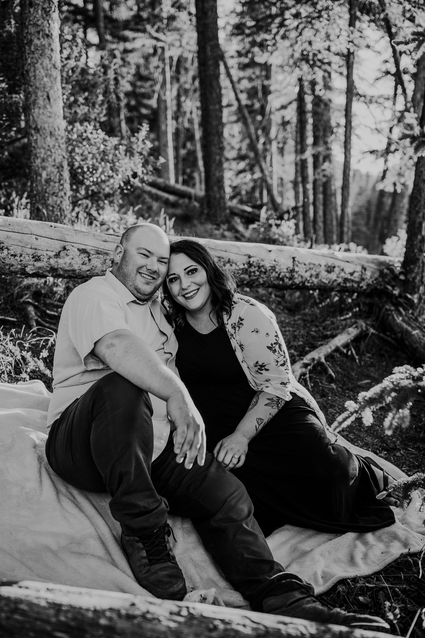 smiling couple sitting on blanket in forest reesor lake alberta