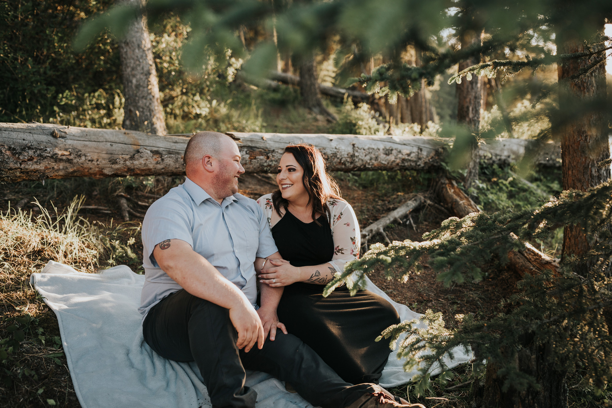 couple sitting on blanket in forest reesor lake alberta engagement