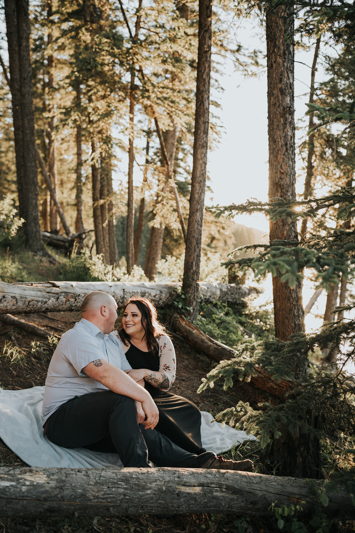 smiling engaged couple sitting on blanket in forest reesor lake alberta