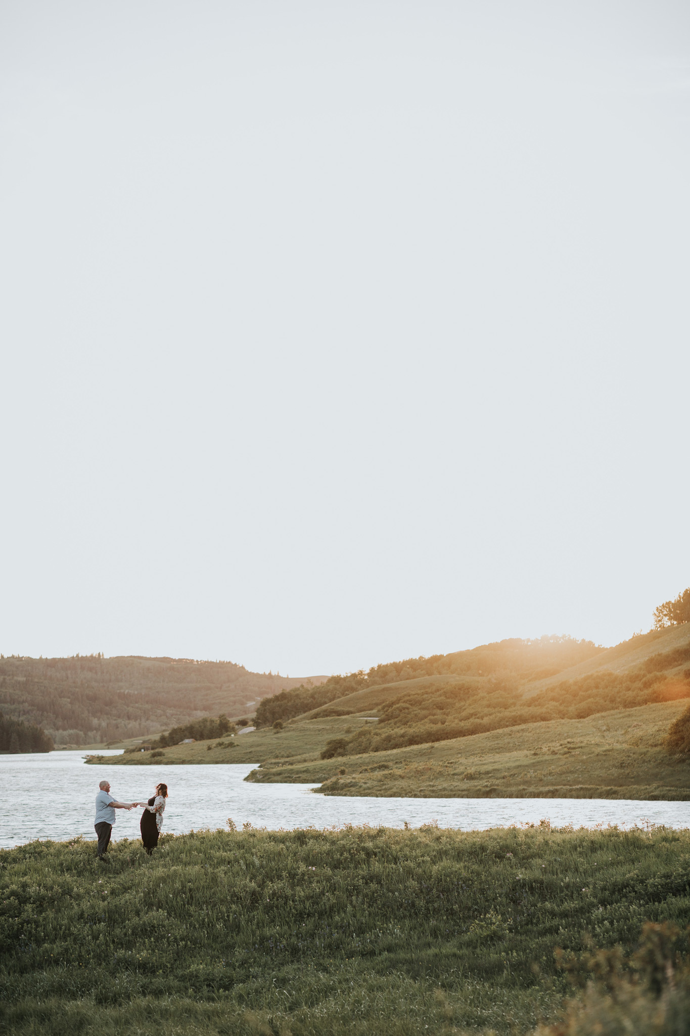 couple dancing beside reesor lake at sunset engagement photo
