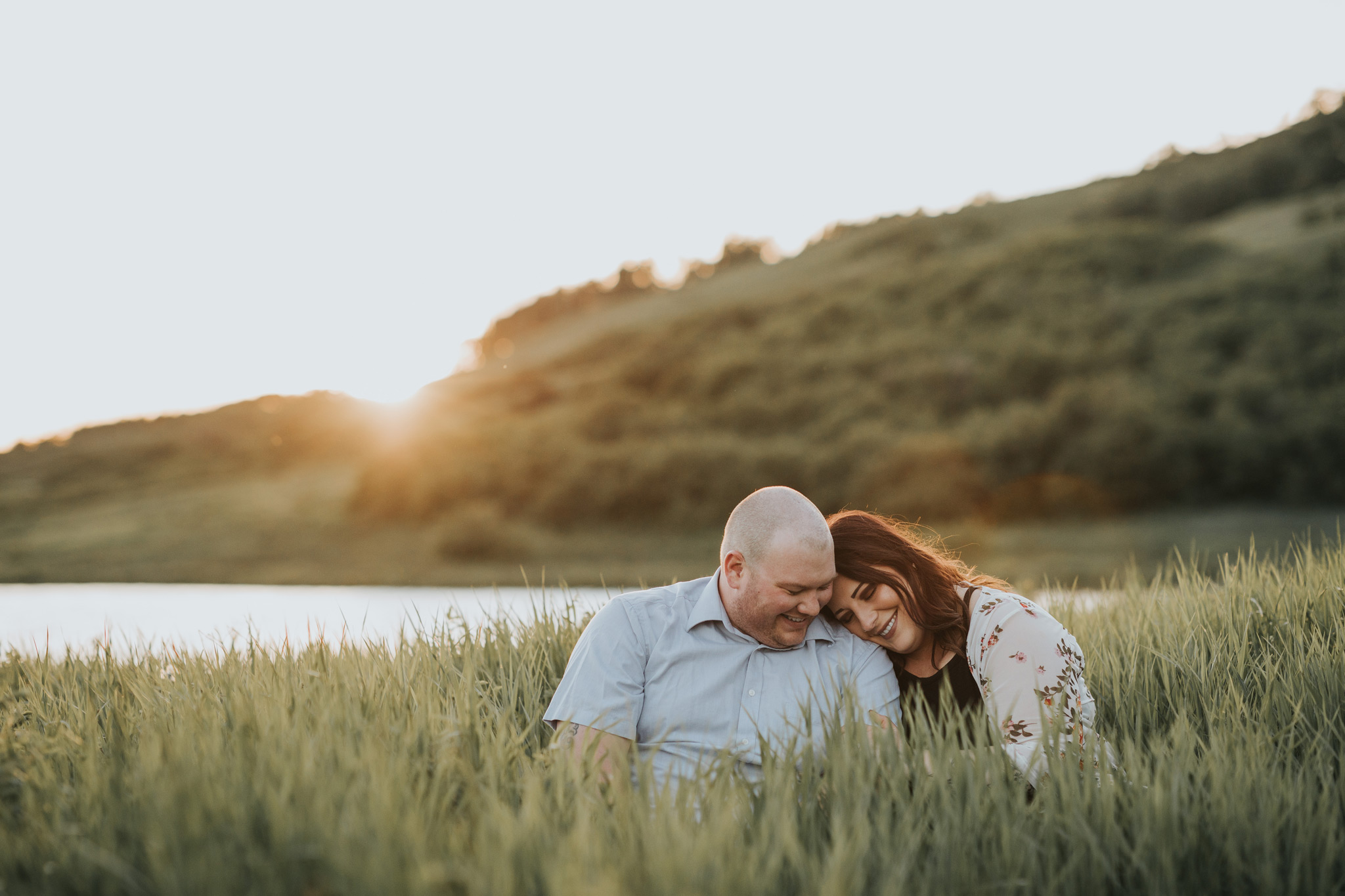 engaged couple sitting in tall grass cuddling reesor lake alberta