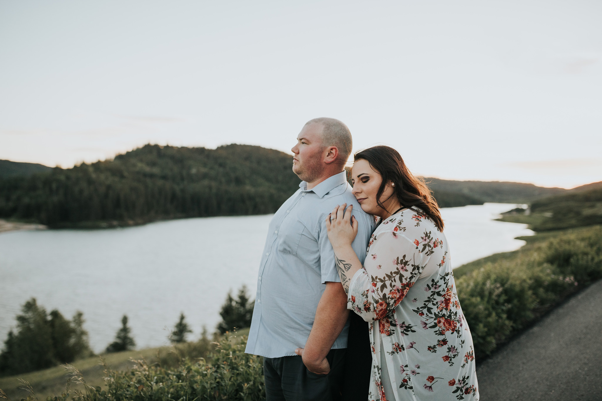 woman embraces fiancé from the back engagement photo view reesor lake alberta