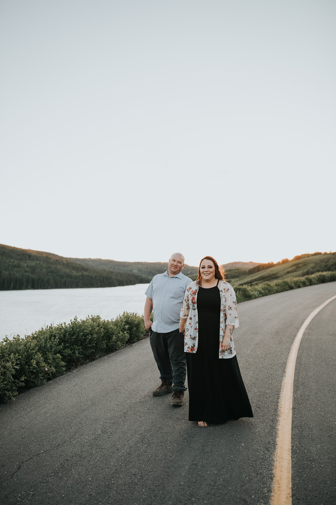happy couple walking on road above reesor lake engagement photo