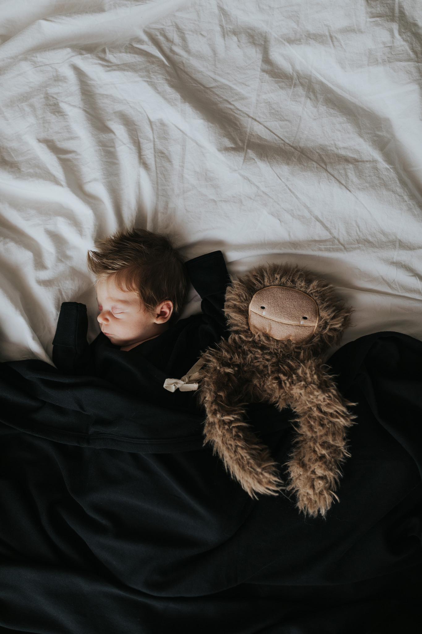 baby sleeping on bed cuddling stuffed animal
