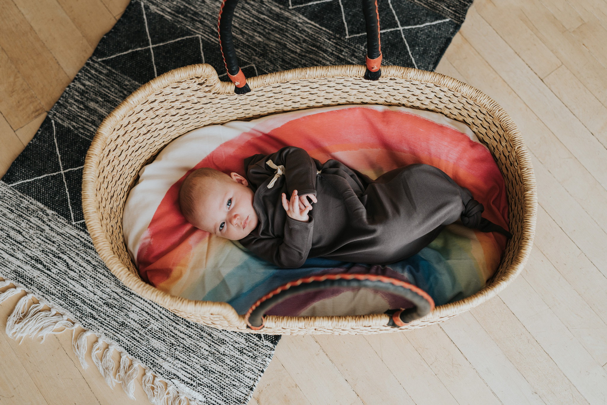 baby laying in bassinet basket with rainbow blanket