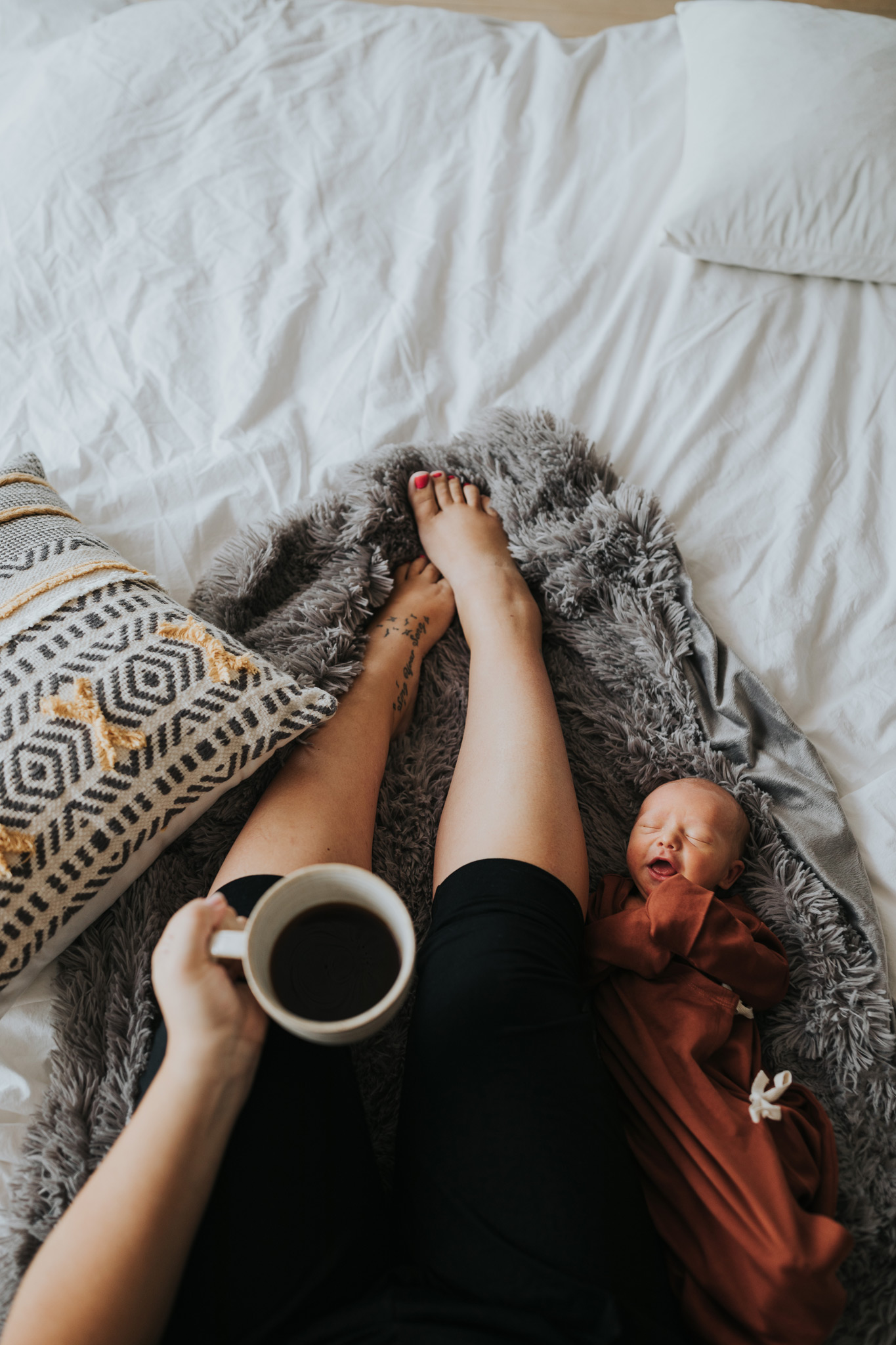 newborn baby laying beside mom as she drinks coffee