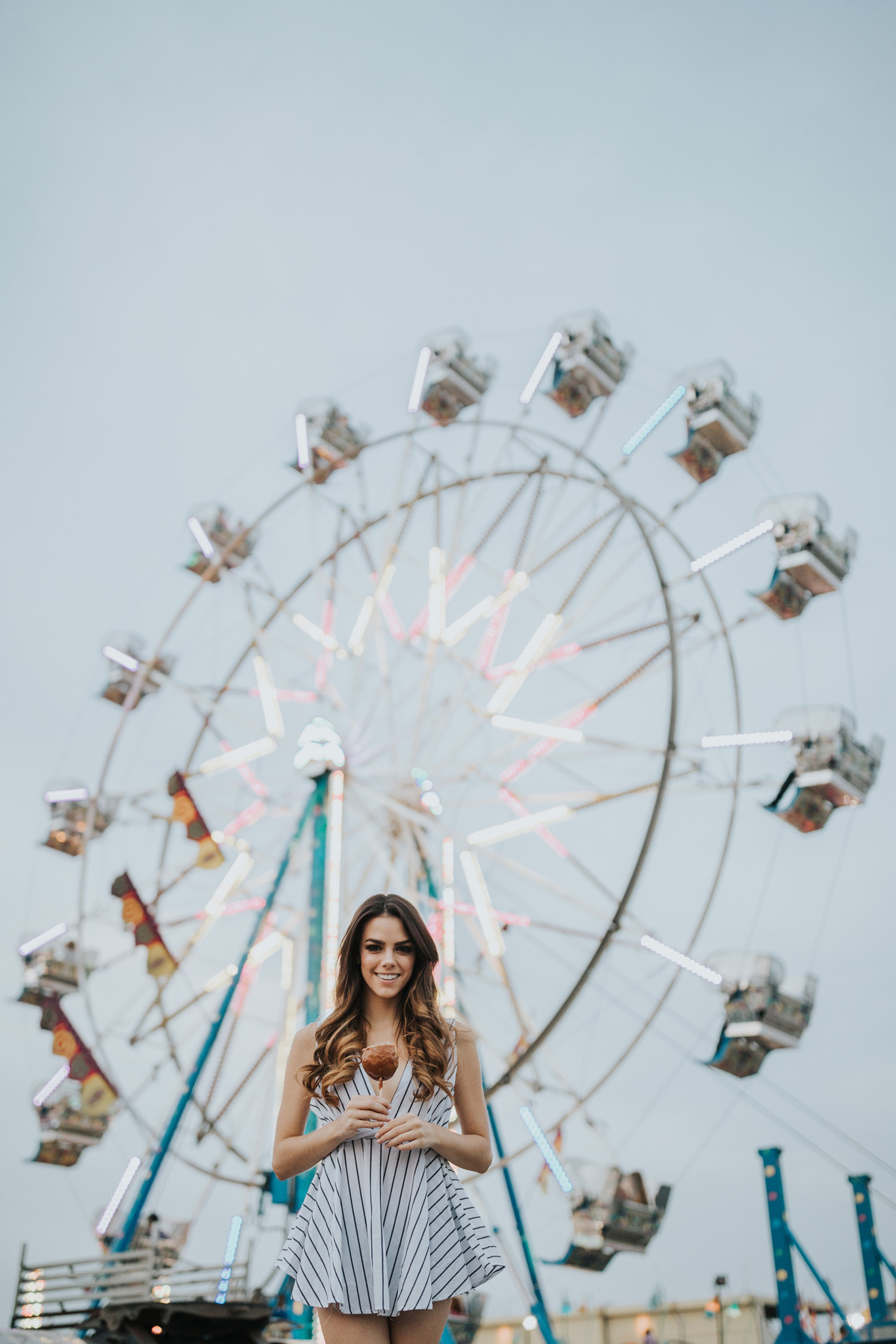 woman holding candy apple in front of ferris wheel medicine hat alberta