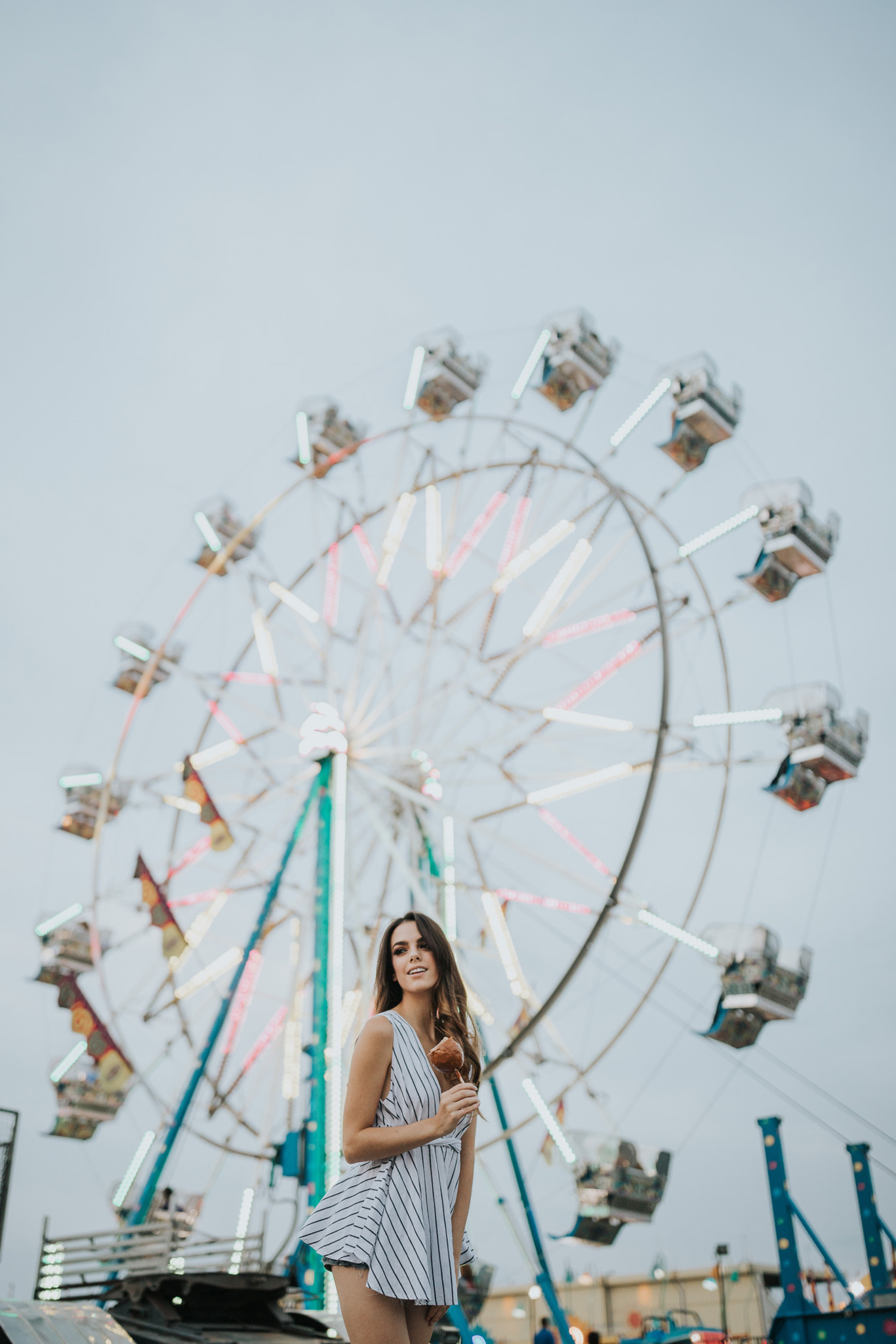 model holding candy apple in front of ferris wheel medicine hat alberta