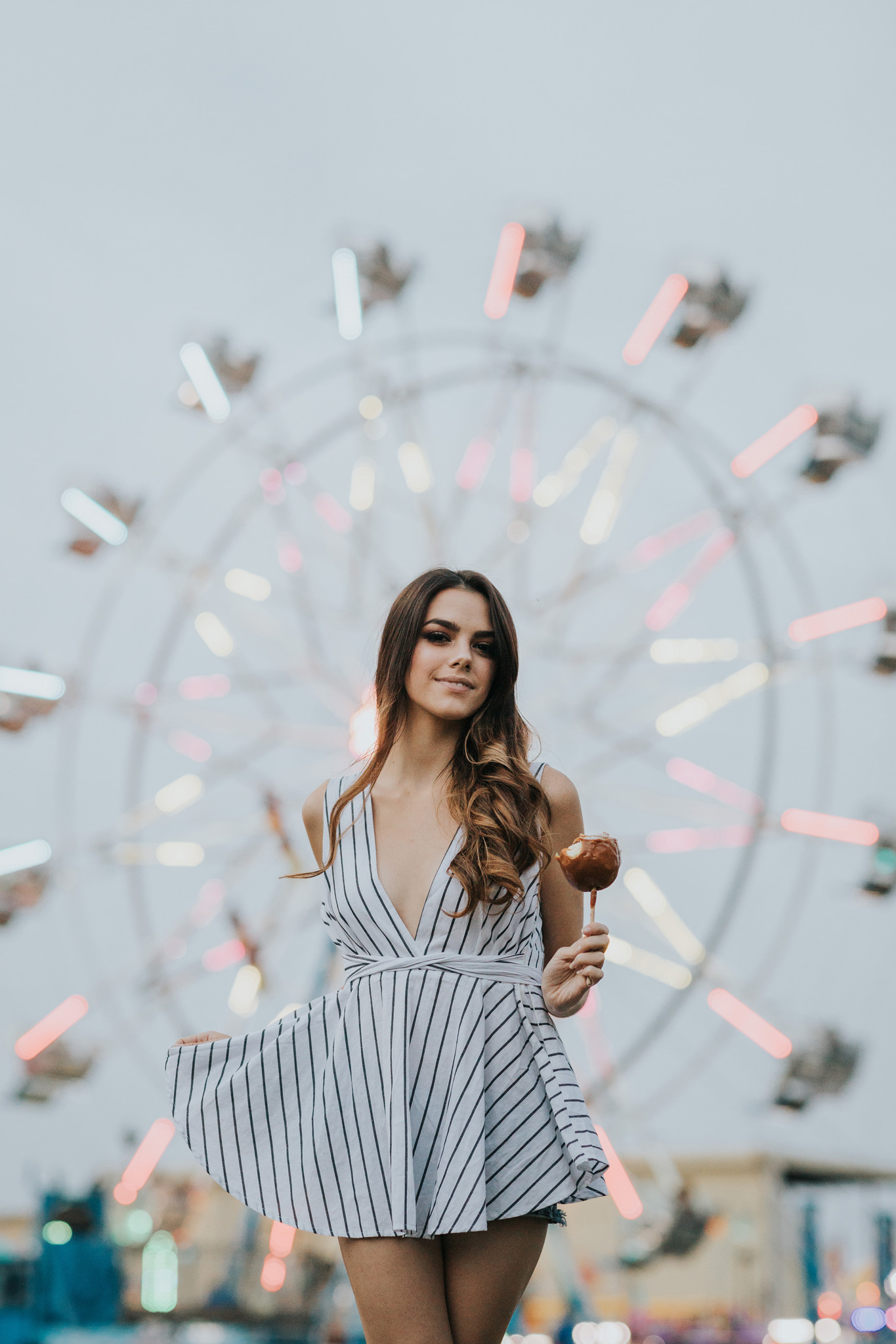 model holding candy apple in front of ferris wheel medicine hat stampede