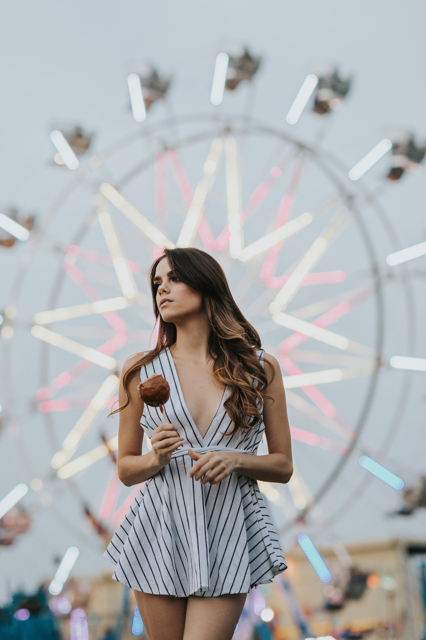 model holding candy apple in front of ferris wheel lights